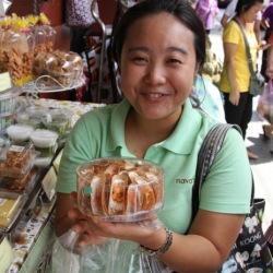 Bangkok Food Tours' smiling guide holding khnom-krok, a Thai treat