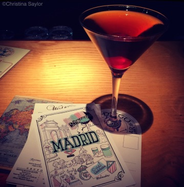 Writing postcards while enjoying a Manhattan in Madrid