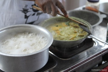 Karuna demonstrating the best way to cook curry