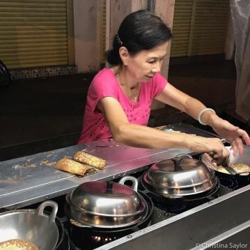 Street food vendor making apam balik at night, Penang