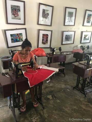 A woman sewing traditional handicraft at Boneca de Ataúro